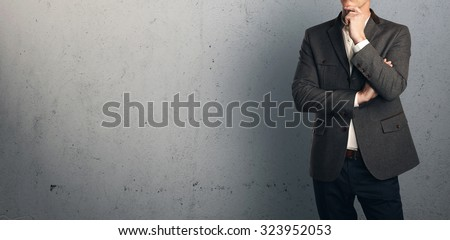 Young businessman thinking on the background of a concrete wall