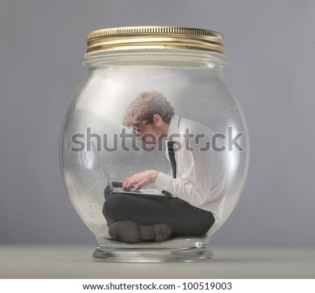Young businessman trapped in a glass jar and using a laptop