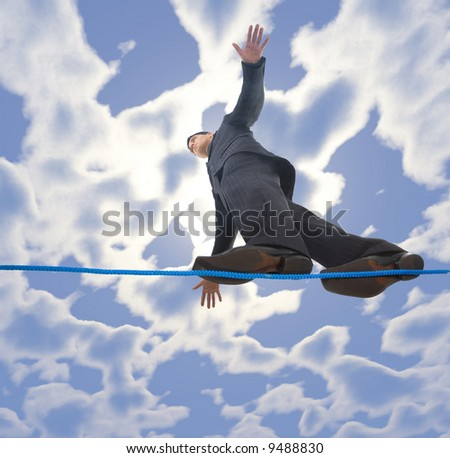 Young businessman walking on line in the air. Holding balance. Low angle view