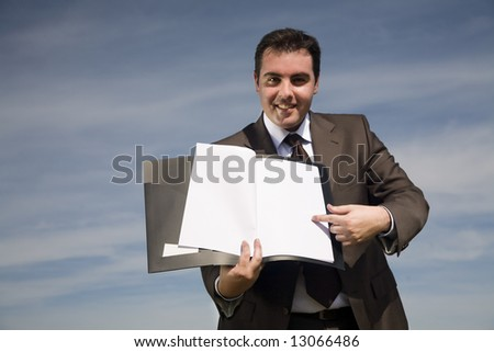 young businessman with corporate binder pointing to blank paper - outdoor environment