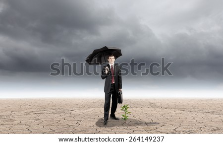 Young businessman with umbrella protecting sprout growing in desert