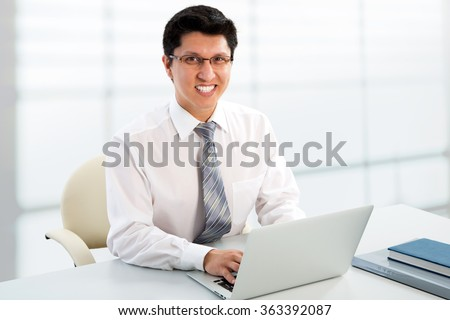 Young businessman working in office with laptop, sitting at desk, looking at camera, smiling.