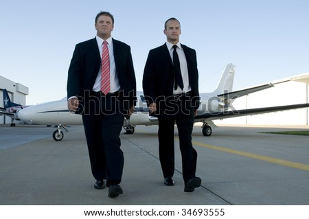 Young businessmen walking away from corporate jet with serious looks.