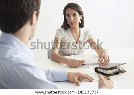 Young businesswoman discussing with male colleague at desk in office