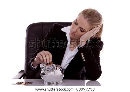 Young businesswoman feeling sad as she put coins in her savings pig.