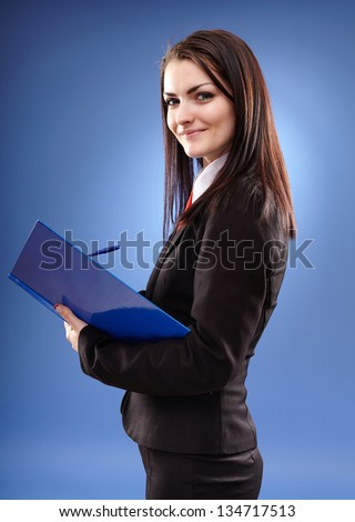 Young businesswoman holding a notebook in her hands in closeup pose, over blue background