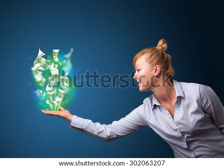 Young businesswoman holding glowing paper moneys in her hand