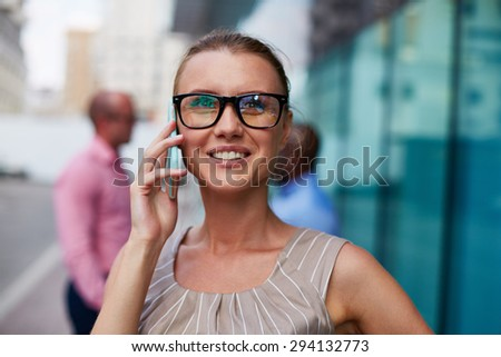 Young businesswoman in eyeglasses speaking on the phone