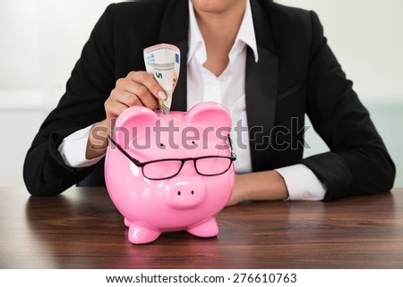 Young Businesswoman Inserting Banknote In Piggybank At Desk