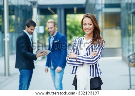 Young businesswoman posing in front of a small group of business people