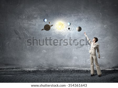 Young businesswoman reaching hand  to space planets