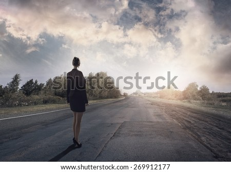 Young businesswoman standing on road and choosing her way