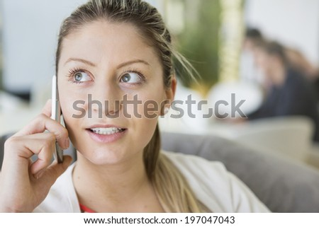 Young businesswoman talking on cell phone in office