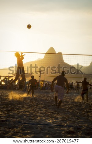 Young carioca Brazilians play a game of beach volleyball against a sunset silhouette of Two Brothers Mountain in Ipanema.