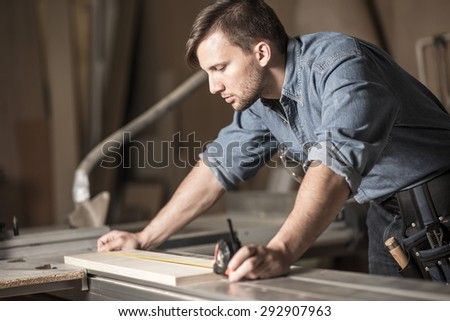Young carpenter using measuring tape at work