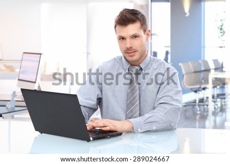 Young caucasian businessman in shirt and tie sitting at office desk using laptop looking up at camera.