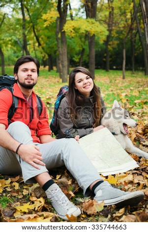 young caucasian couple hiking with siberian husky dog. Hikers with map and compass in autumn wood