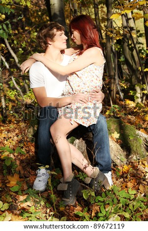Young caucasian couple sitting on big stone in forest and looking at each other eyes.