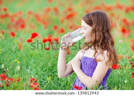 Young Caucasian girl drinking a glass of water in field