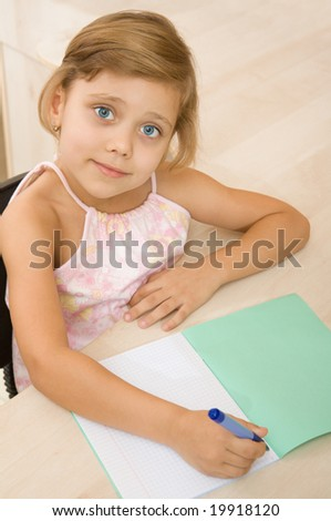 Young caucasian girl writing in a notebook