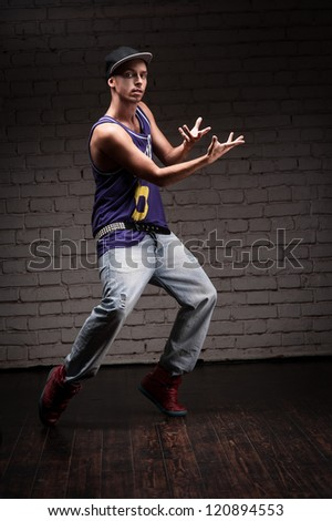 young caucasian male hip-hop dancer showing some moves over brick wall background