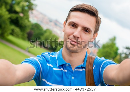Young caucasian man making selfie background european old city by mobile phone from the observation place