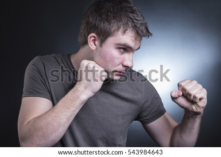 Young caucasian, white male standing in a fight stance, fists raised, strong and confident
