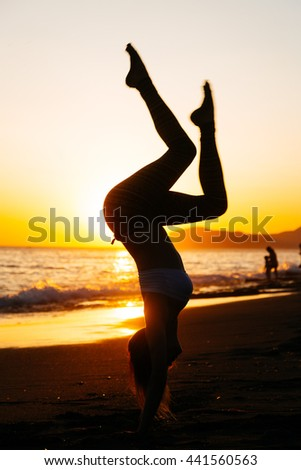 Young caucasian woman standing on her hands at the beach of mediterranean sea