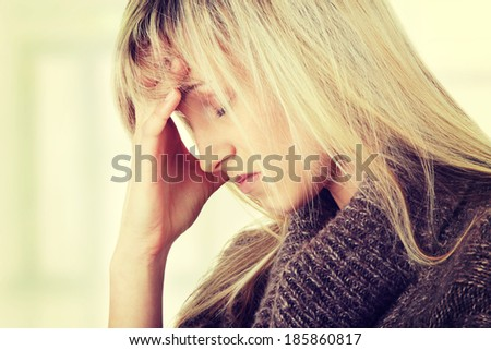 Young caucasian woman (student or businesswoman) with severe Migraine Headache holding hands to head