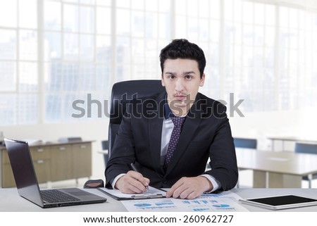 Young caucasian worker wearing formal suit and look at the camera while working on the table
