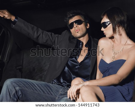 Young celebrity couple wearing sunglasses in limousine