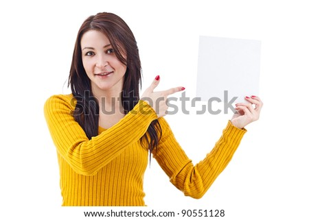 Young charming woman in yellow pointing a blank page over white background