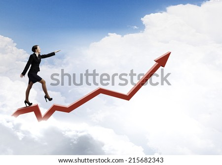 Young cheerful businesswoman walking on increasing graph