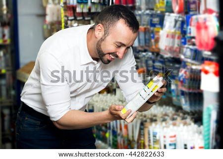 Young cheerful man choosing sealant tube in household store