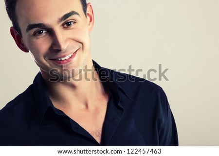 Young cheerful man in black shirt, portrait of attractive guy looking at camera