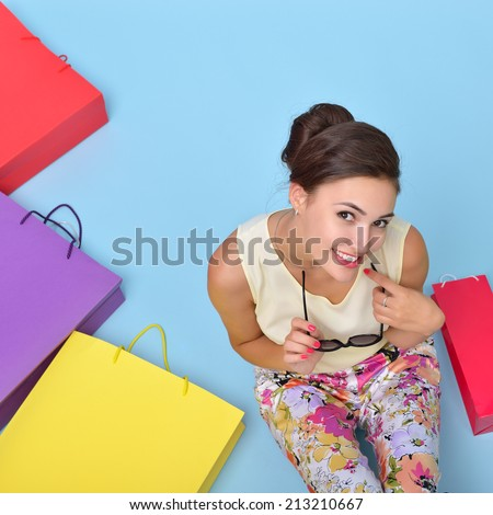 Young cheerful woman with colored paper shopping bags. Shopaholic. Shopping concept and ideas. Urban lifestyle.
