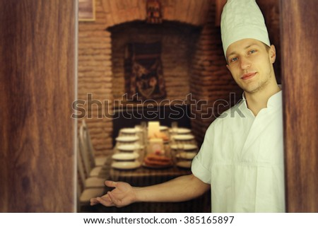 Young Chef With Arm Out In A Welcoming Gesture