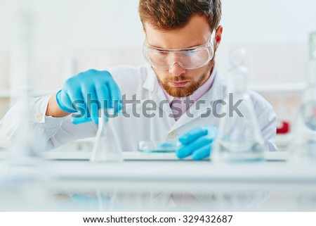 Young chemist mixing up liquids in laboratory