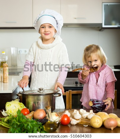 Young children learn how to prepare food indoors. Wearing casual clothes and a chef's hat