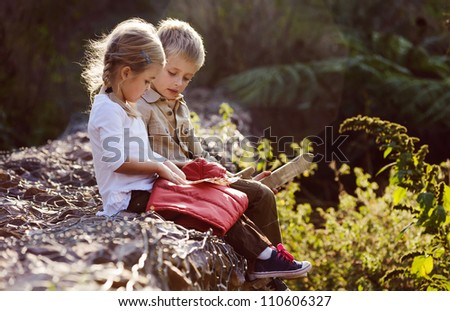 young children playing outdoors, happy brother and sister having fun