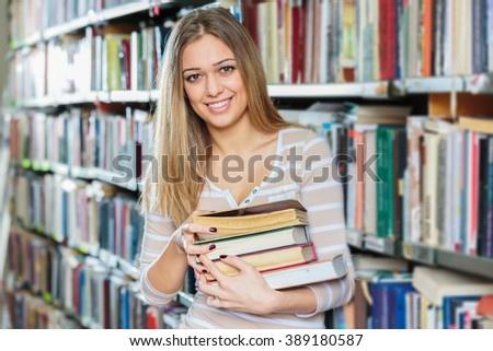 Young college woman in library holding books .