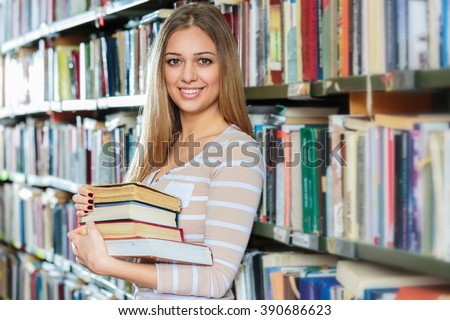 Young college woman in library holding books.