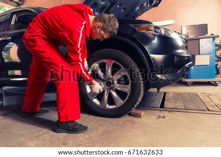 Young concentrated male auto mechanic standing near a black sedan and screwing car wheel by wrench in auto repair service