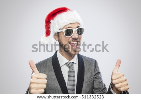 Young cool elegant man with Santa Claus hat and sunglasses