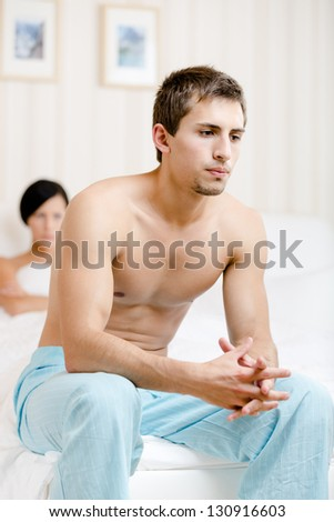 Young couple argues in bed-room. Depressed man sitting on the edge of the bed. Focus on man