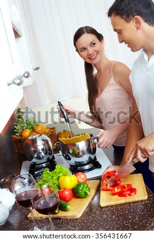 Young couple cooking spaghetti and salad in the kitchen