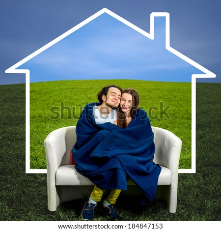 Young couple dreaming about new house sitting in the couch at the green field and drawing the shape of a house