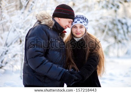 young couple have a walk in the winter park
