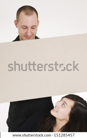 young couple hold an empty sign / millboard