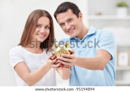 Young couple holding hands in the piggy bank